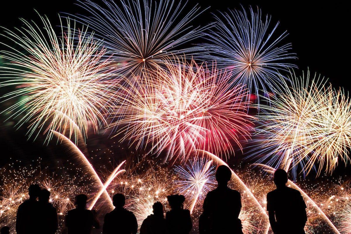 Großes buntes Feuerwerk mit den Schatten der Menschen im Vordergrund