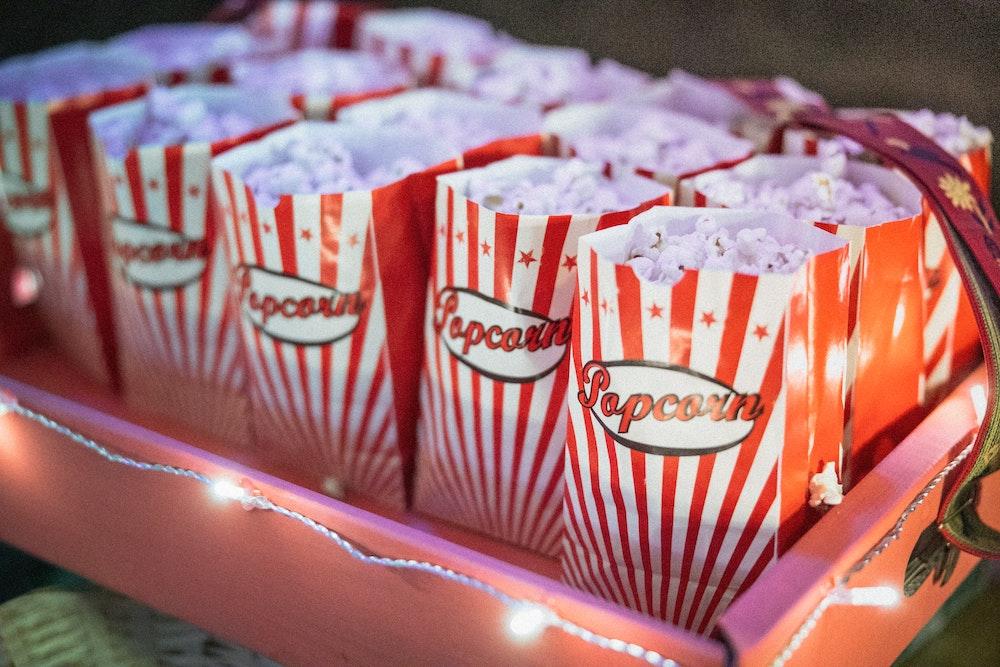 Viele rot weiß gestreifte und gefüllte Popcorntüten auf einem Tablett umgeben von einer kleinen Lichterkette
