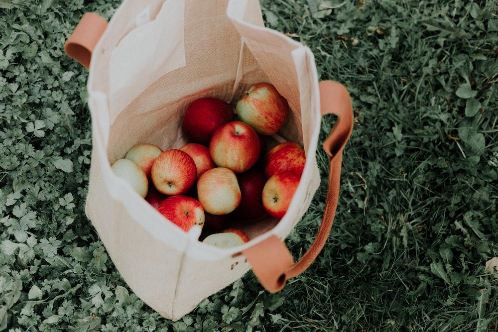 Ein Haufen frischer Äpfel in einem Leinenbeutel auf dem Gras